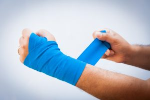 an injury, man bandaging his arm